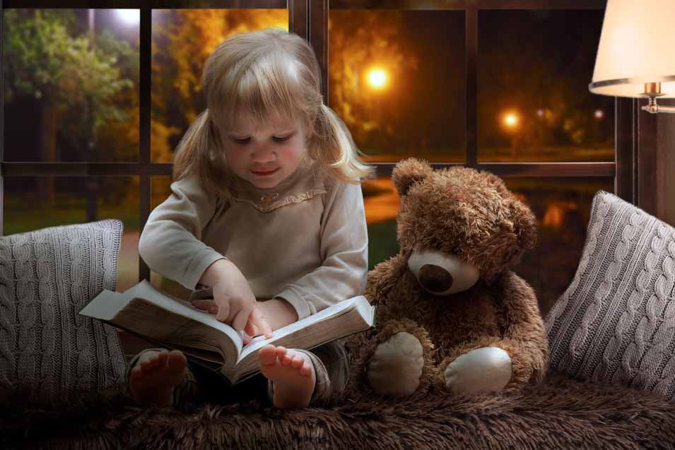 Picture of a girl reading to her teddy bear